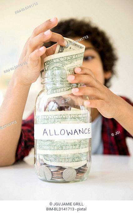Mixed race boy putting allowance in savings jar