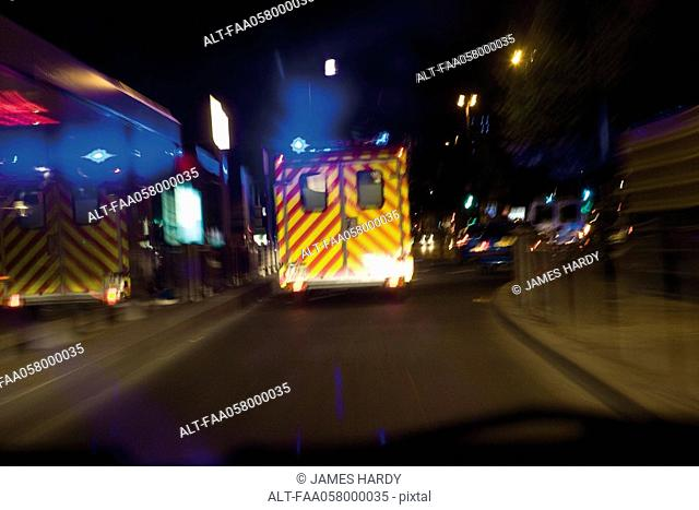 Ambulance driving on street at night