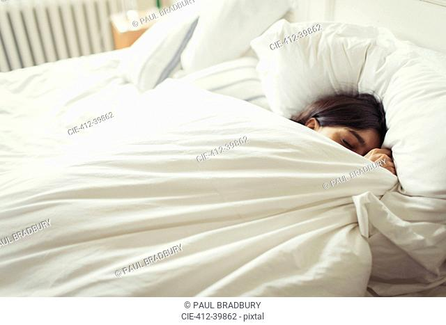 Tired young woman sleeping in bed