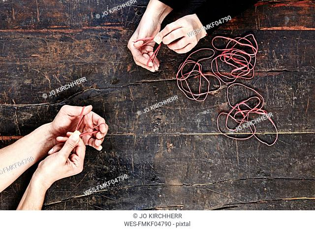 Hands of man and woman playing with rubber bands, top view