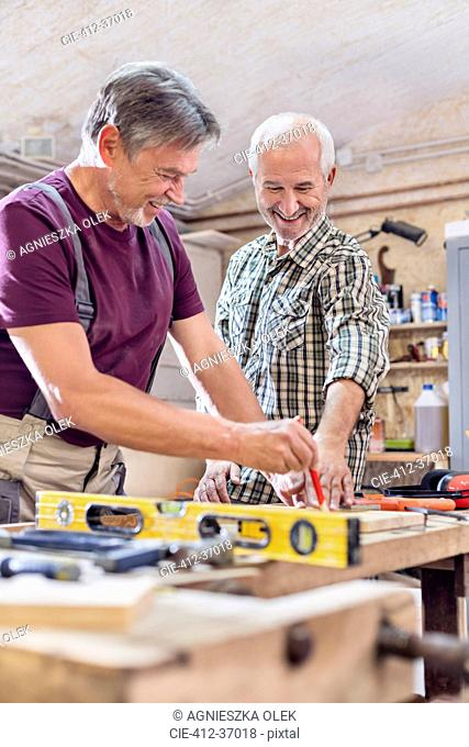 Smiling male carpenters measuring and marking wood on workbench in workshop