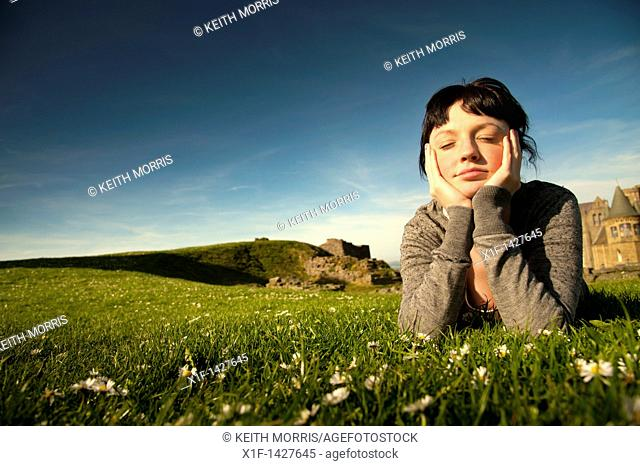 A young woman lying on the grass outdoors with her head in her hands daydreaming on a spring summer afternoon  UK
