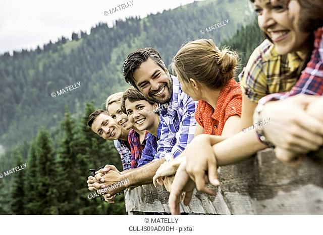 Group of friends leaning on wooden fence, Tirol, Austria
