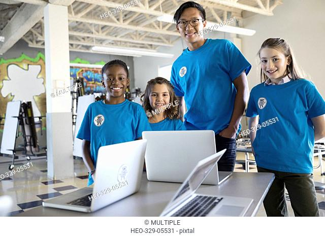 Portrait confident male teacher and pre-adolescent girls at laptops in classroom