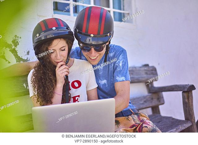 Young couple using mobile laptop during break at road trip. Hersonissos, Crete, Greece