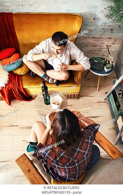 Young couple eating chinese take-away food at home