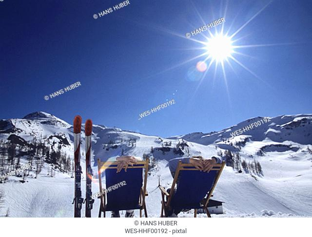Man and woman relaxing in alps, rear view