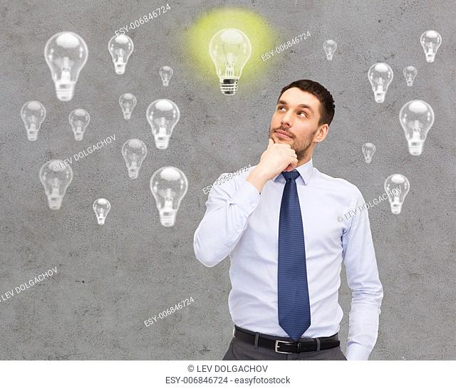 business, ideas, inspiration and people concept - handsome businessman looking up and thinking over concrete background with light bulbs