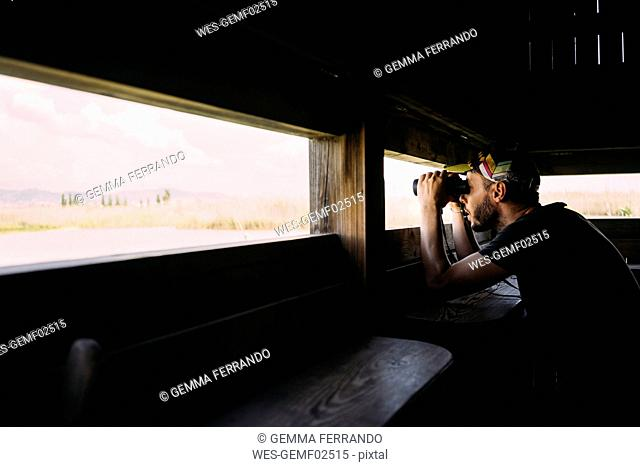 Man birdwatching with binoculars from a viewing tower