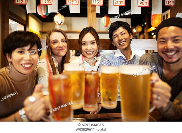 Five people sitting sidy by side at a table in a restaurant, holding large glasses with beer