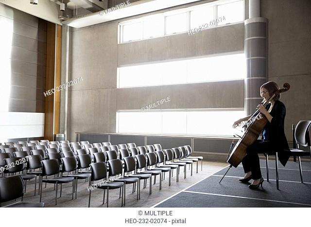 Female cellist practicing on stage in empty auditorium