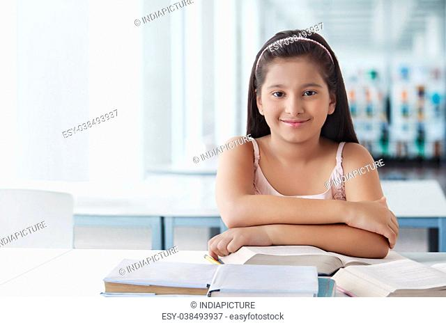 Portrait of cute girl at desk with books