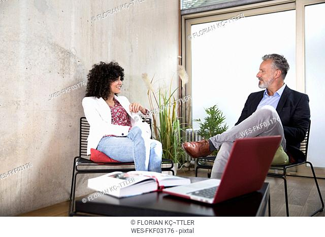 Businessman and businesswoman sitting in a loft at concrete wall smiling
