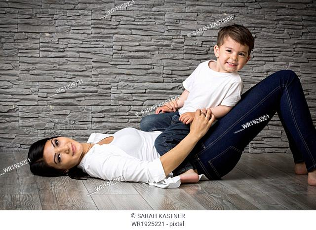 Mother and son cuddling on the floor