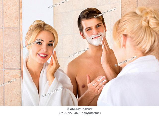 Portrait Of A Man Shaving And Her Wife Cleaning Her Face In Mirror At Bathroom