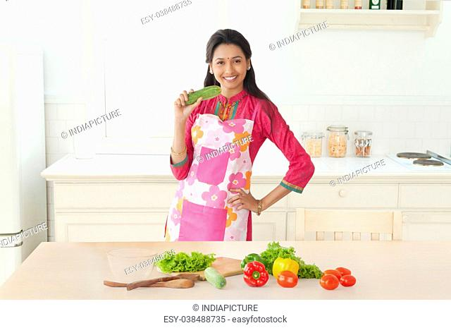 Woman holding cucumber in kitchen