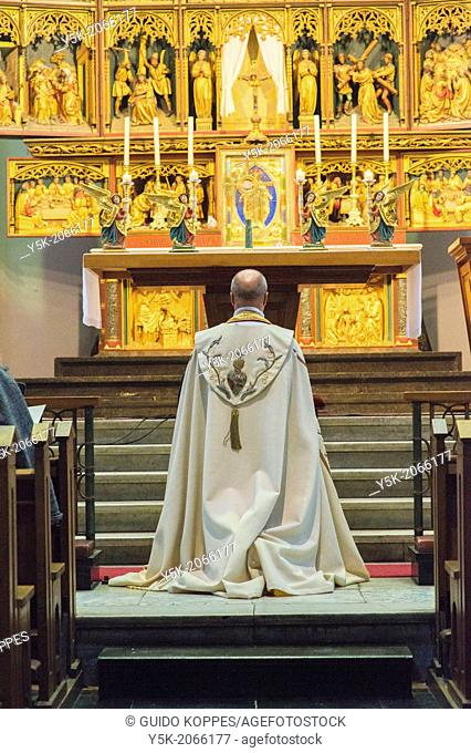 Tilburg, Netherlands. A chaplain praying before his believers in a roman catholic church