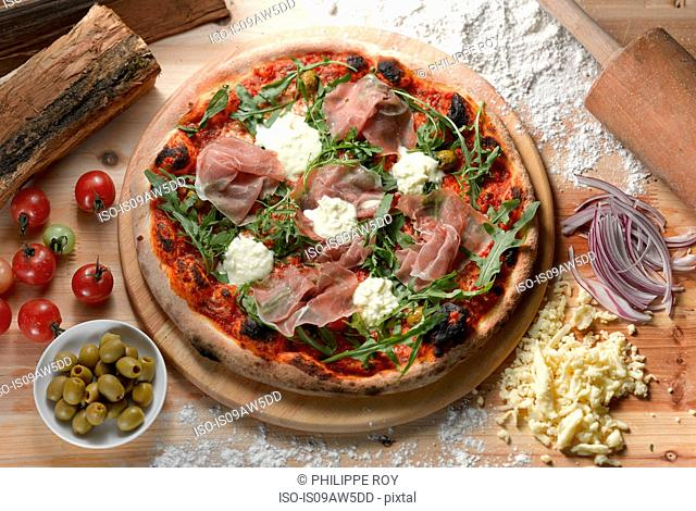 Overhead view of parma ham pizza with green olives