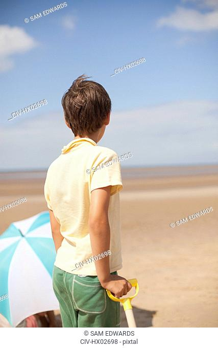 Pensive boy looking away on sunny summer beach