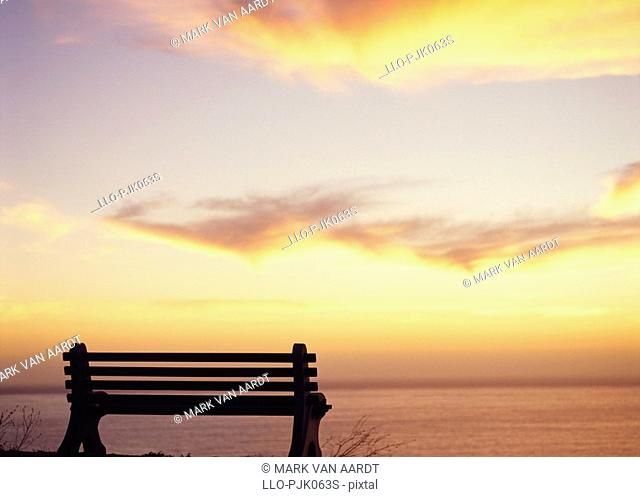 Bench at Sunset over the Atlantic Ocean off Clifton. Cape Peninsula, Cape Town, Western Cape Province, South Africa