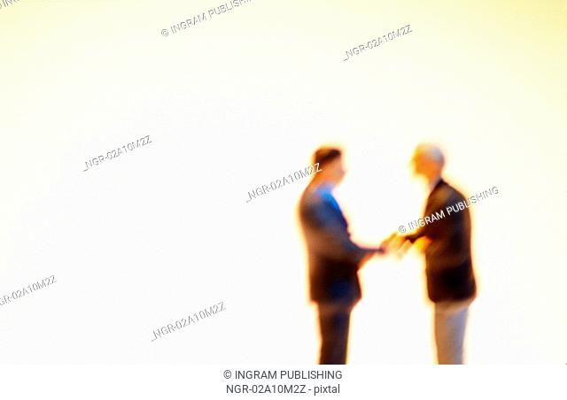 Two miniature male figures shaking hands