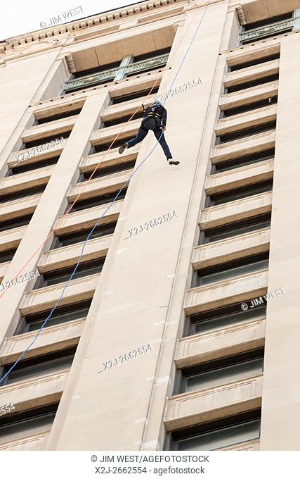 Detroit, Michigan - People rappel down the 25-story First National Building as a fundraiser to benefit charities in Detroit and Nepal