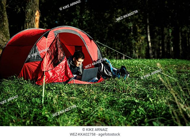 Man camping in Estonia, sitting in his tent, using laptop