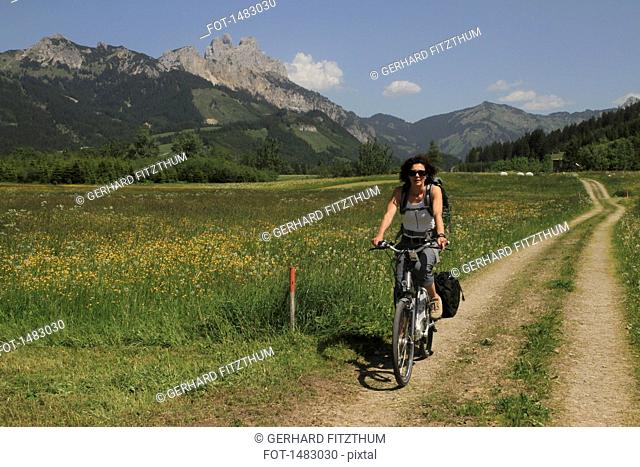Woman riding bicycle on road by grassy field against mountains