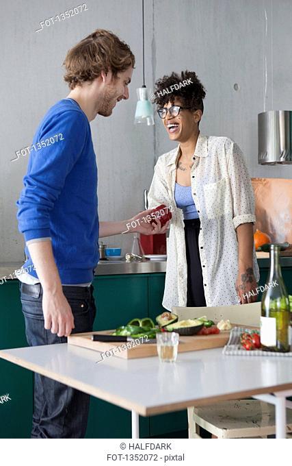 Happy friends preparing food in kitchen