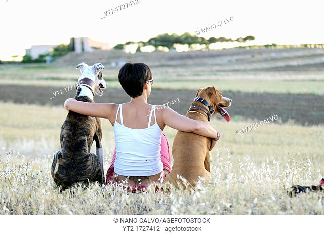 Young woman sitting in nature with her dogs, at sunset