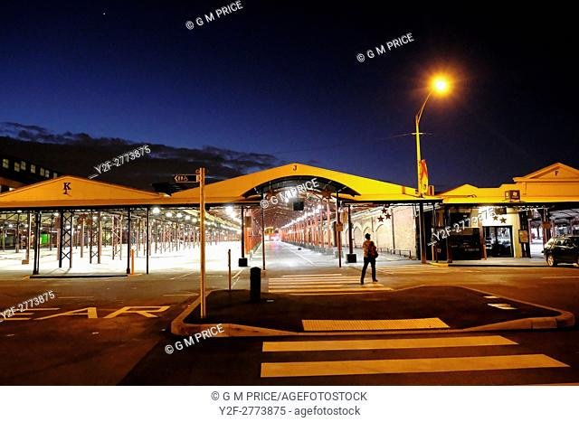 man walking at dusk through empty Queen Victoria Market, Melbourne