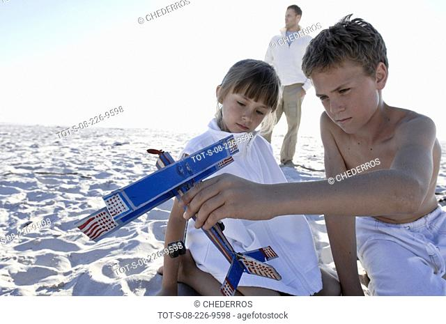 Close-up of a boy and his sister sitting on the beach with their father standing behind them