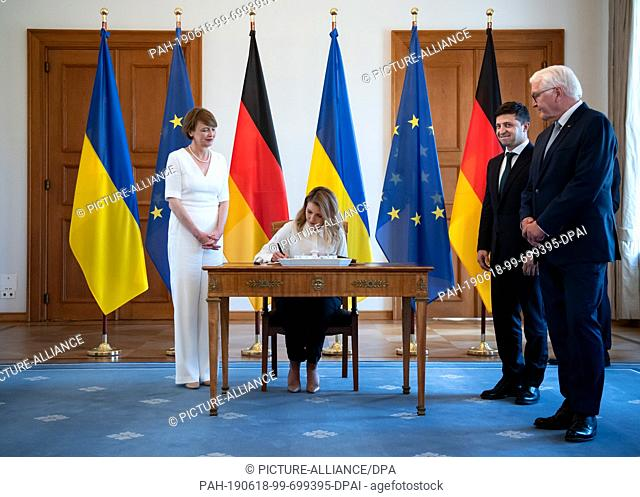 18 June 2019, Berlin: Olena Selenska (2nd from left) enters her name in the guestbook at Bellevue Castle in the presence of her husband