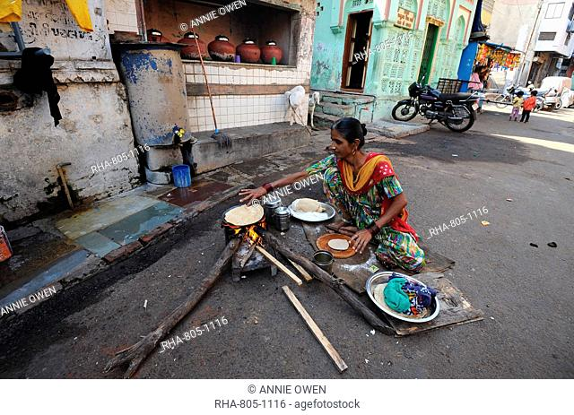 Woman making the day's chapatis on a wood fire in the street outside near the Jama Mosque in old Ahmedabad, Gujarat, India, Asia
