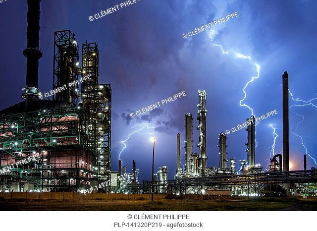 Lightning bolts striking over oil refinery at industrial estate during heavy thunderstorm at night, conceptual picture for global warming due to carbon dioxide...