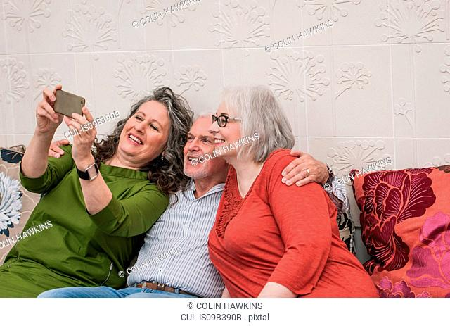 Happy seniors taking selfie on couch