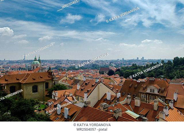 View of Prague with red tile roofs and the green domes of St Nicholas Cathedral in the distance
