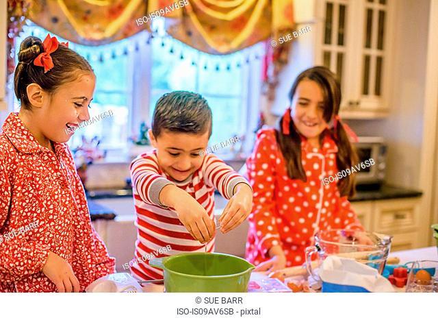 Children in kitchen wearing pyjamas cracking eggs into mixing bowl smiling
