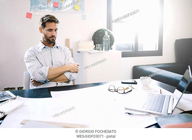 Portrait of pensive architect sitting at desk