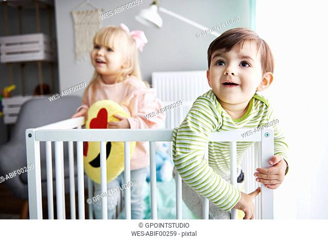 Portrait of smiling toddler standing in crib with his sister in the background