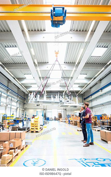 Manager and warehouse worker looking up at winch in distribution warehouse