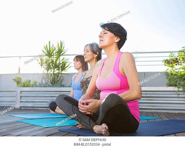 Women meditating together on rooftop
