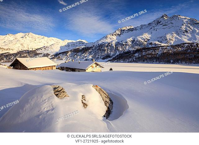 Huts and mountains covered in snow at sunset Spluga Maloja Canton of Graubünden Engadin Switzerland Europe