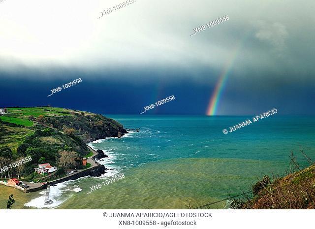 Cargadero de Mioño y playa de Dicido Cantabria con el arco iris de fondo, en un día de tormenta sobre un mar de color esmeralda