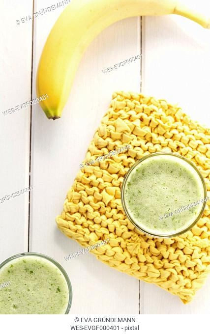 Two glasses of curly cale banana smoothie, yellow potholder and banana on white wooden table, elevated view