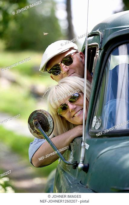 Smiling mature couple looking through cars window