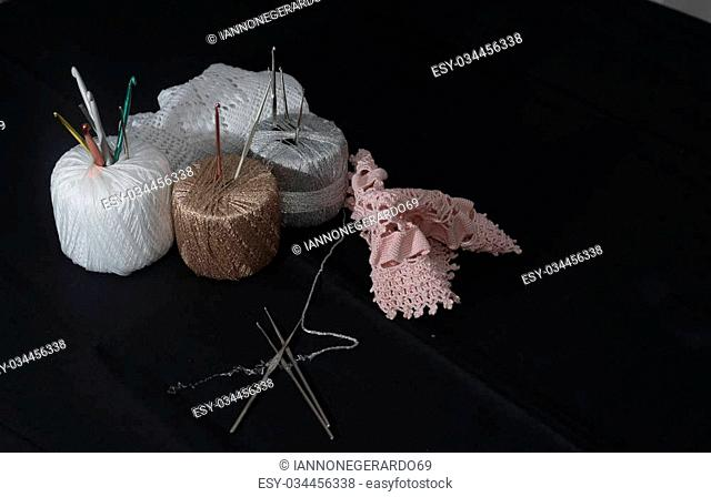 Crochet, Italian manufacture. made in Italy. Balls of yarn and crochet for the work of the school of Italian craftsmanship. black background