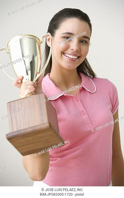 Portrait of teenage girl posing with trophy