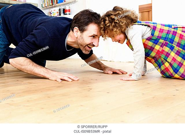 Mature man crawling head to head with daughter on kitchen floor