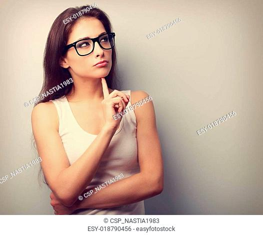 Serious fun thinking young woman looking up on empty copy space
